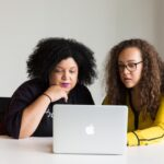 Two women looking at the screen of a Macbook. Credits: Christina - wocintechchat.com. Unsplash.